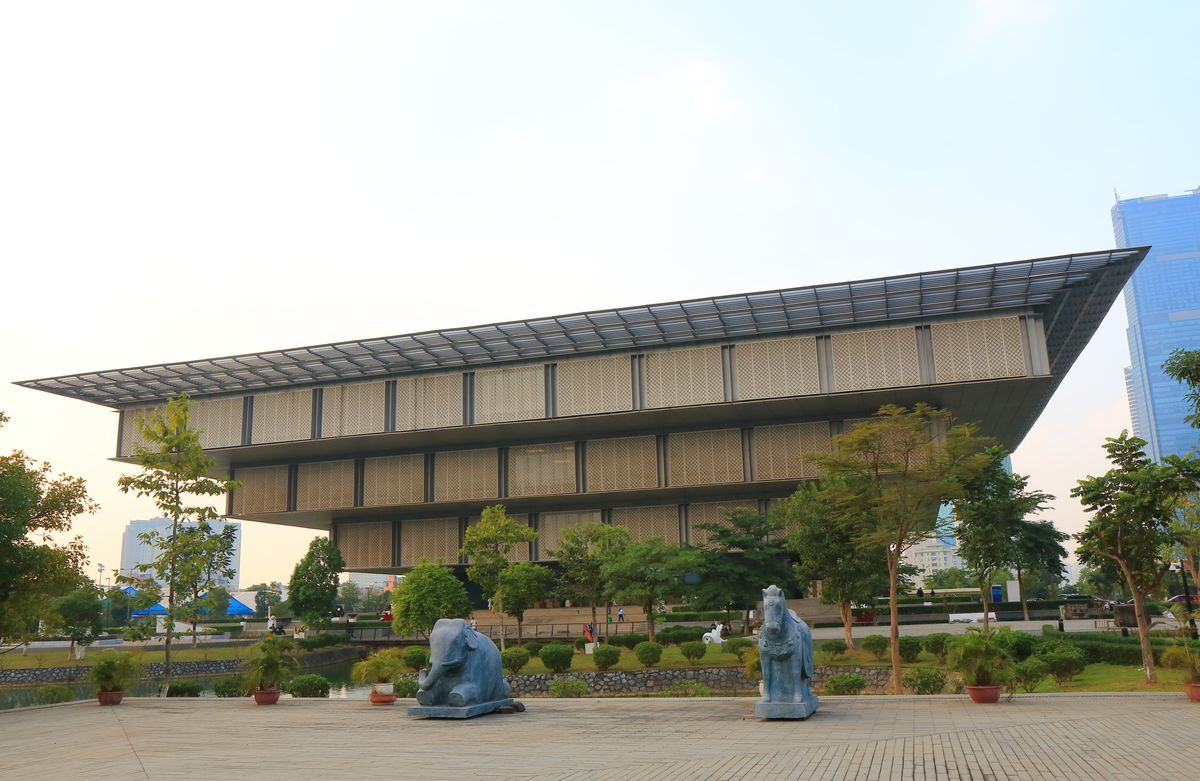 The exterior of the Hanoi Museum in Vietnam. The building is shaped like an inverted pyramid. There are sculptures of animals in the foreground.