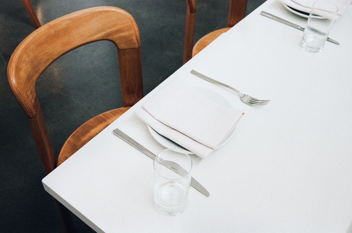 A wooden chair and white table in a new restaurant.