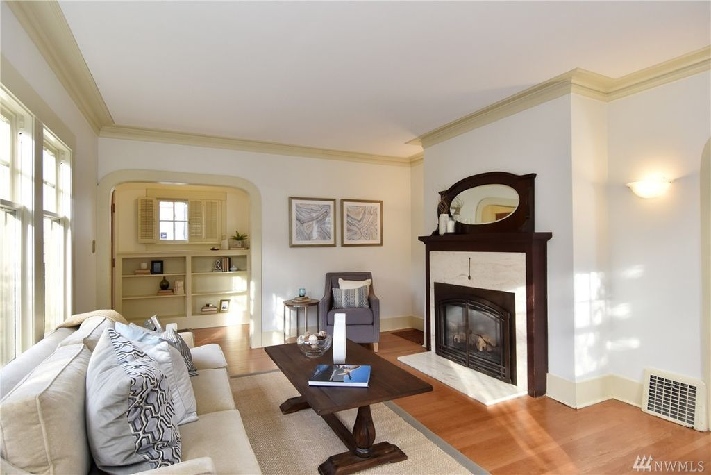 A living area with an arched doorway leading to some built-ins. A fireplace with white stone and a dark wood mantle is along the wall to the right.