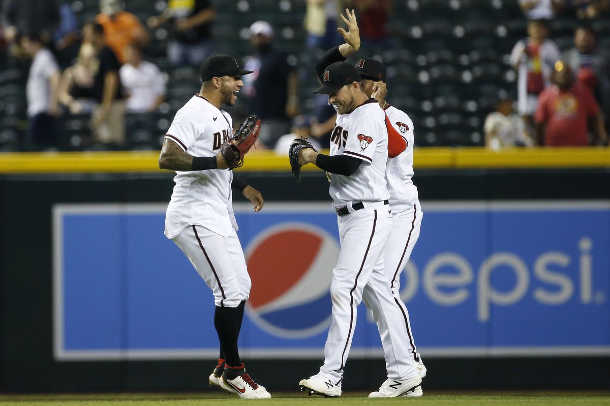 Peralta, Reddick, and Heath celebrate in the outfield following the Diamondbacks win against the Giants.