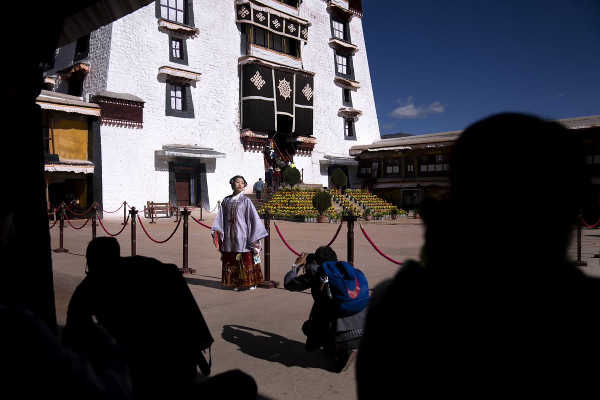 A Chinese tourist in Tibetan dress poses for a photo in a courtyard at the Potala Palace in Lhasa in western China's Tibet Autonomous Region.