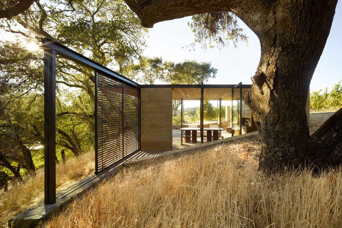 The exterior of Quintessa Estate in California. The structure is surrounded by trees and tall grass. There are floor to ceiling windows. Inside are tables and chairs.