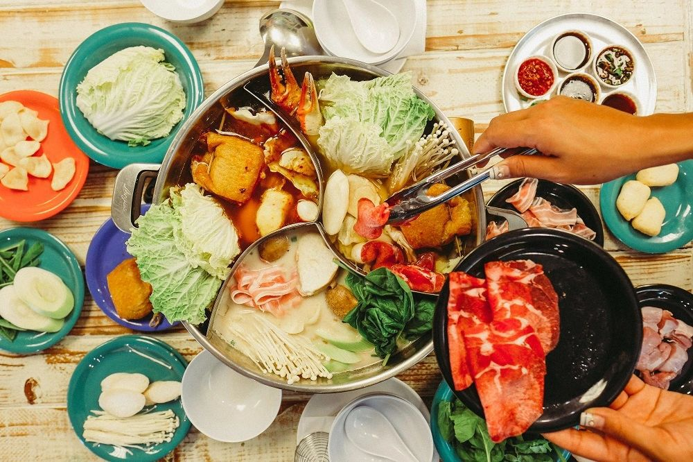 From above, a segmented hot pot overloaded with vegetables, seafood, and meat, with a hand adding more ingredients with tongs, and other condiments and ingredients spread out on the table