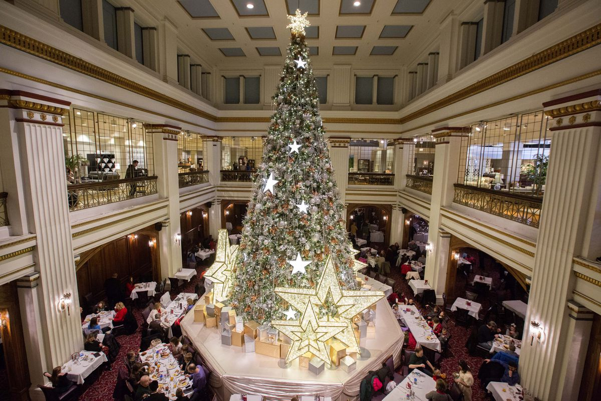 A two story room with a giant Christmas tree surrounded by dining tables and a second floor balcony.