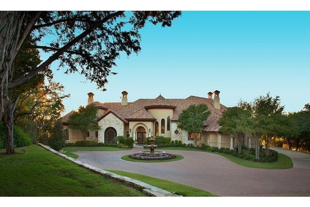 A sprawling, Mediterranean-style mansion with circular driveway