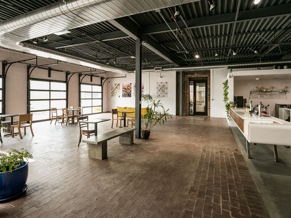 open, empty airy space with wood floors and a few tables