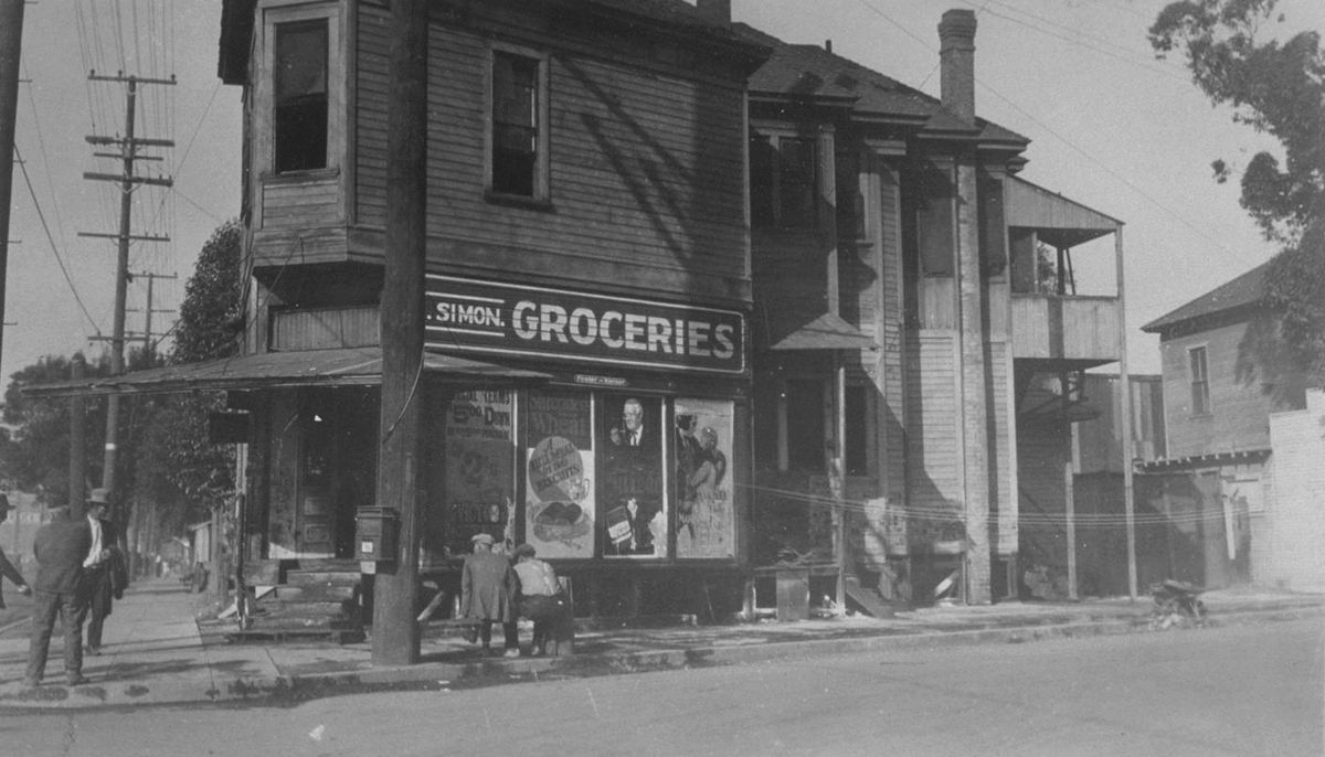 """An archival image of corner grocery store with an awning and a sign that reads """"Simon Groceries."""""""