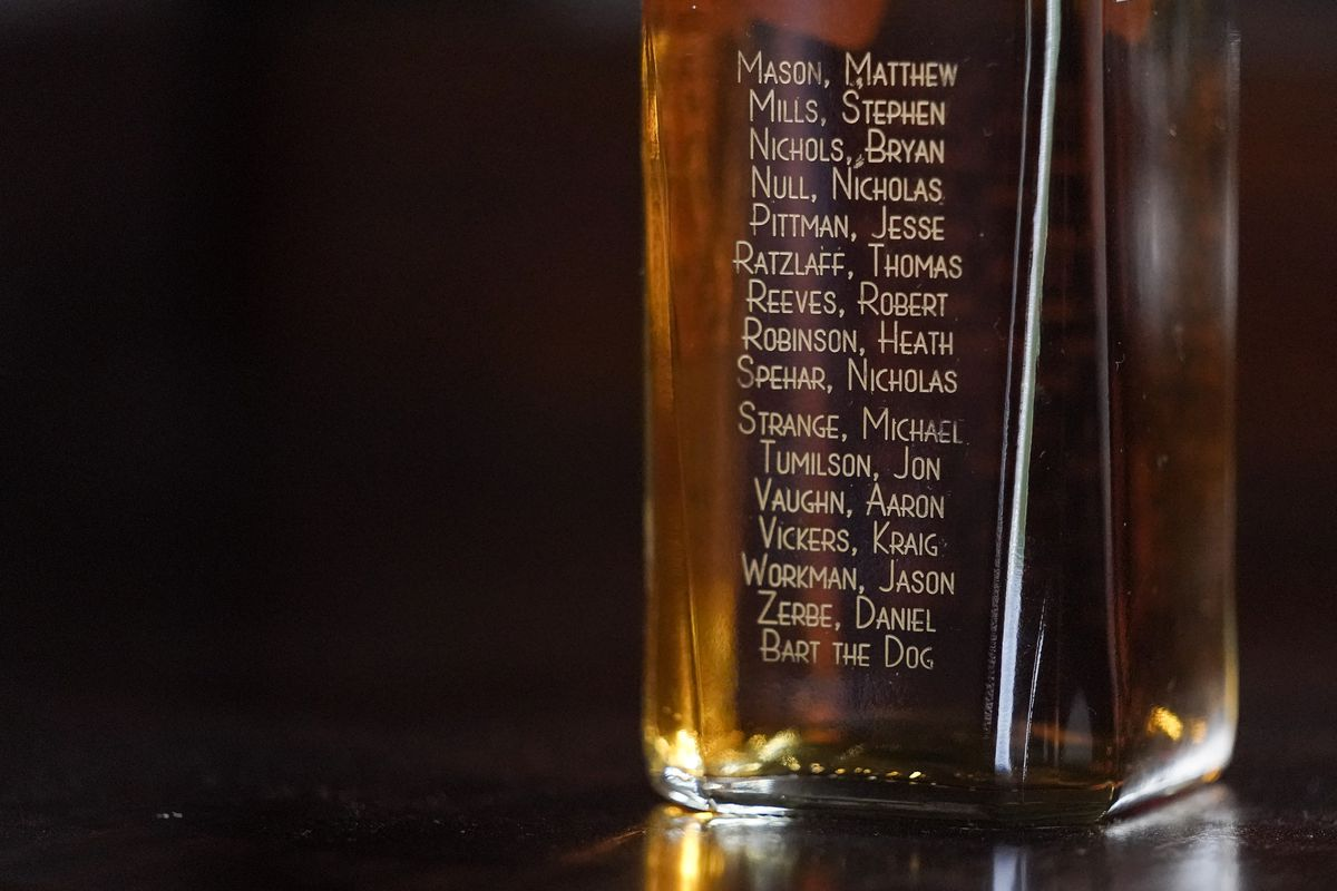 The names of servicemen who died when their Chinook helicopter was shot down in 2011 in Afghanistan are seen on a liquor bottle.