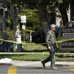 A police official walks past the Maplewood Apartments after a shooting in Lakeside, Calif. Tuesday, Sept. 25, 2012. The San Diego County sheriff's Capt. Duncan Fraser said two deputies and a suspect have been shot while the deputies were trying to contact a child abuse suspect at the suburban apartment complex.