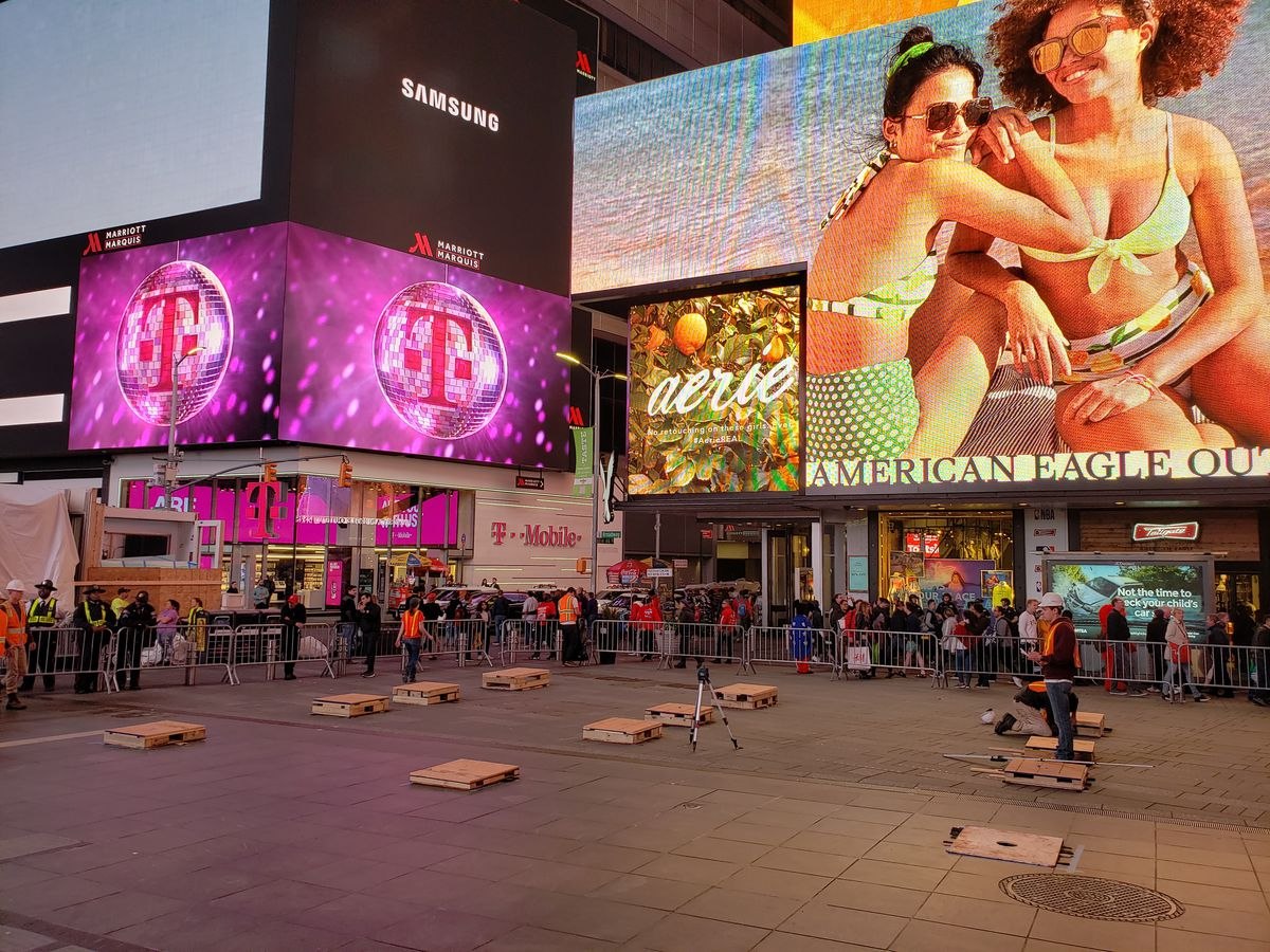 A plaza in Times Square is in the foreground. In the background are billboards and lights on the buildings.