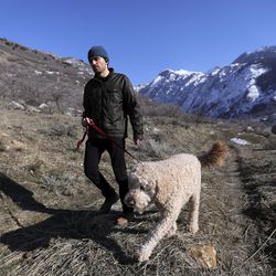 George Stahl walks Henry on the Bonneville Shoreline Trail near the mouth of Little Cottonwood Canyon in Cottonwood Heights on Friday, Feb. 21, 2020. Utah Open Lands is trying to raise funds to preserve a 26-acre parcel of land, including this section of the trail, and prevent development.