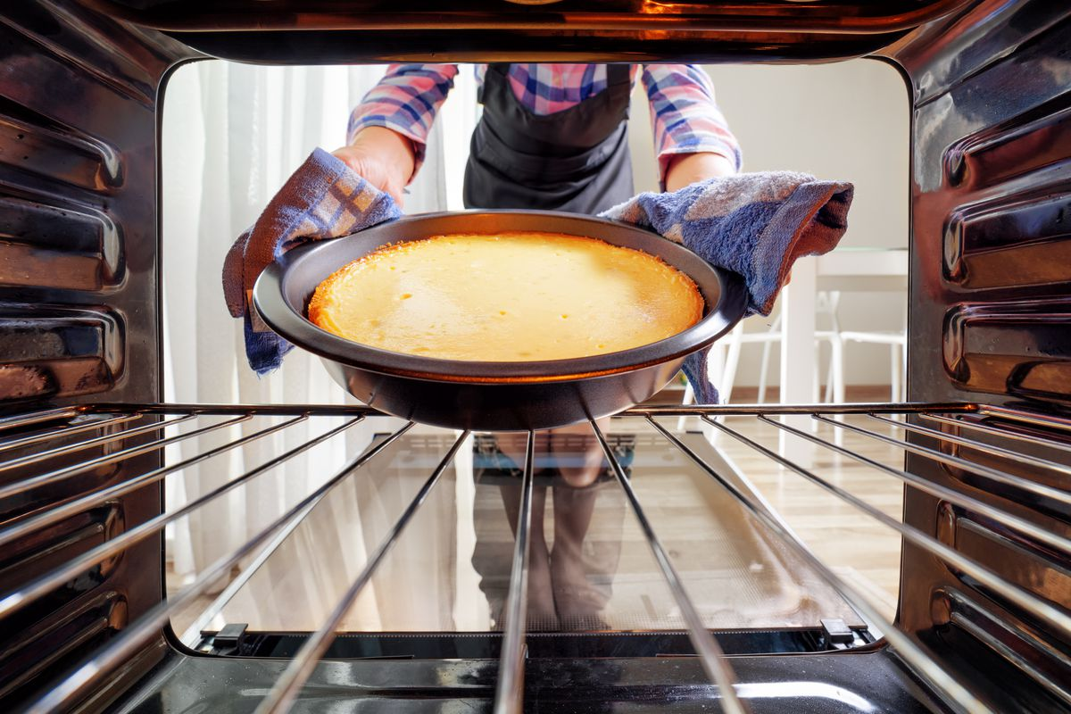 A baker pulls a cake out of the oven