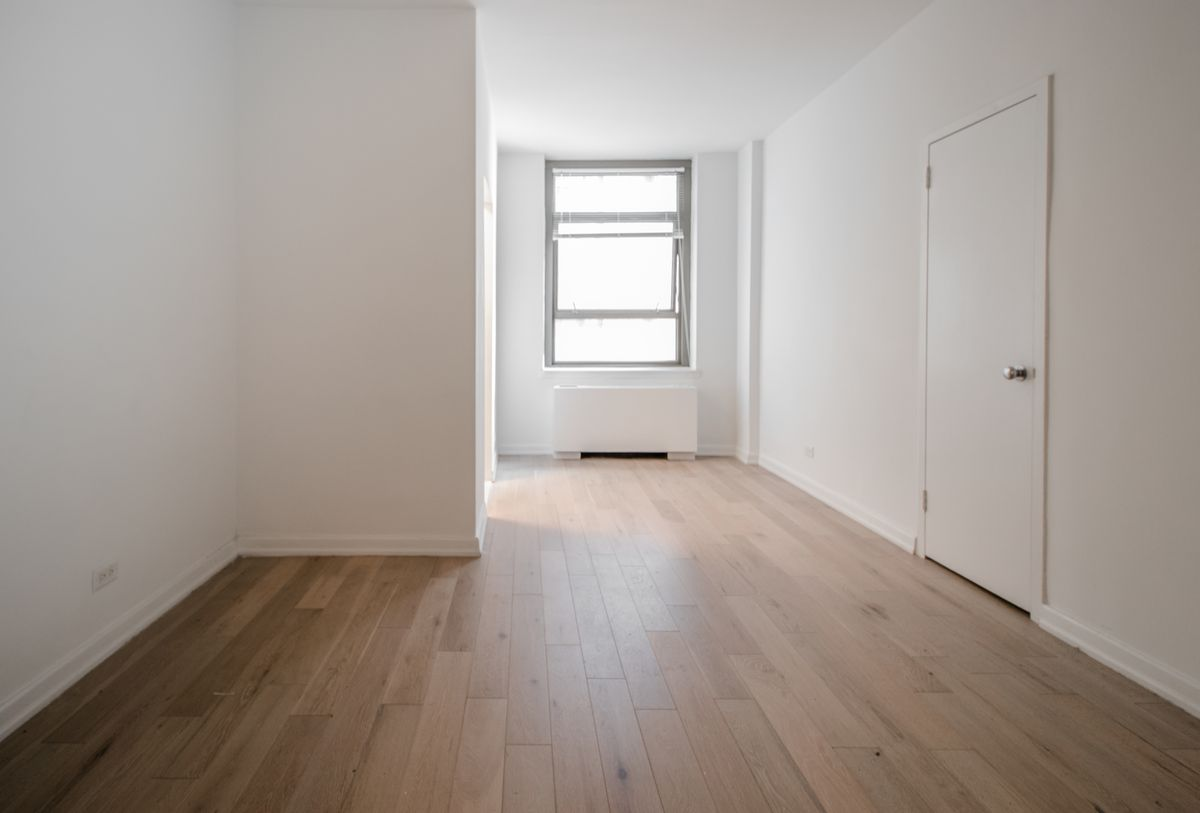 A bedroom with a window, hardwood floors, and white walls.