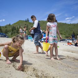 """Mylee Bezzant, 6, left, digs more sand out of her handmade """"waterfall"""" on the beach at Tibble Fork Reservoir on Thursday, June 15, 2017."""