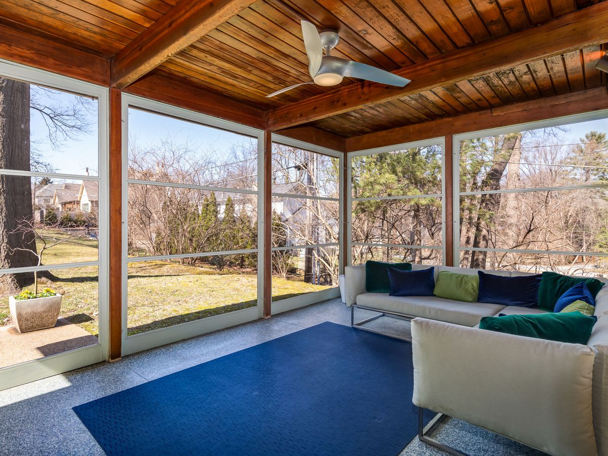 An enclosed patio has a couch, rug, and windows looking out to the yard.