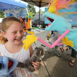 Ann-Ellise Phinney has some fun looking over the puppets during the Sugar House Farmers Market in Sugar House Park in Salt Lake City  Friday, July 5, 2013.