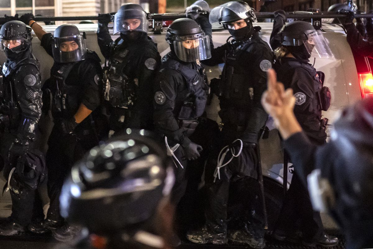 A protester raises their middle finger at a group of heavily armored Portland police officers riding on a troop transport vehicle.