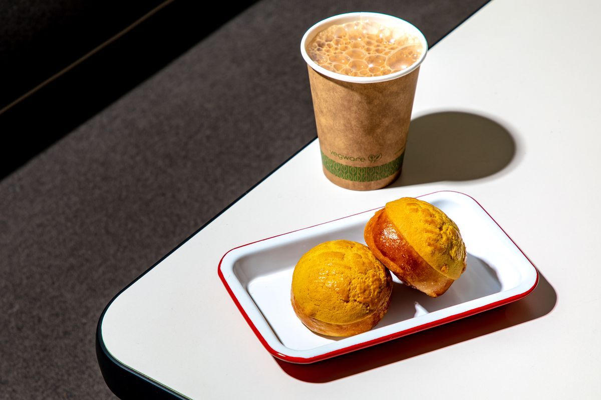Frothy Hong Kong-style milk tea sits adjacent yellow pineapple buns on a white table