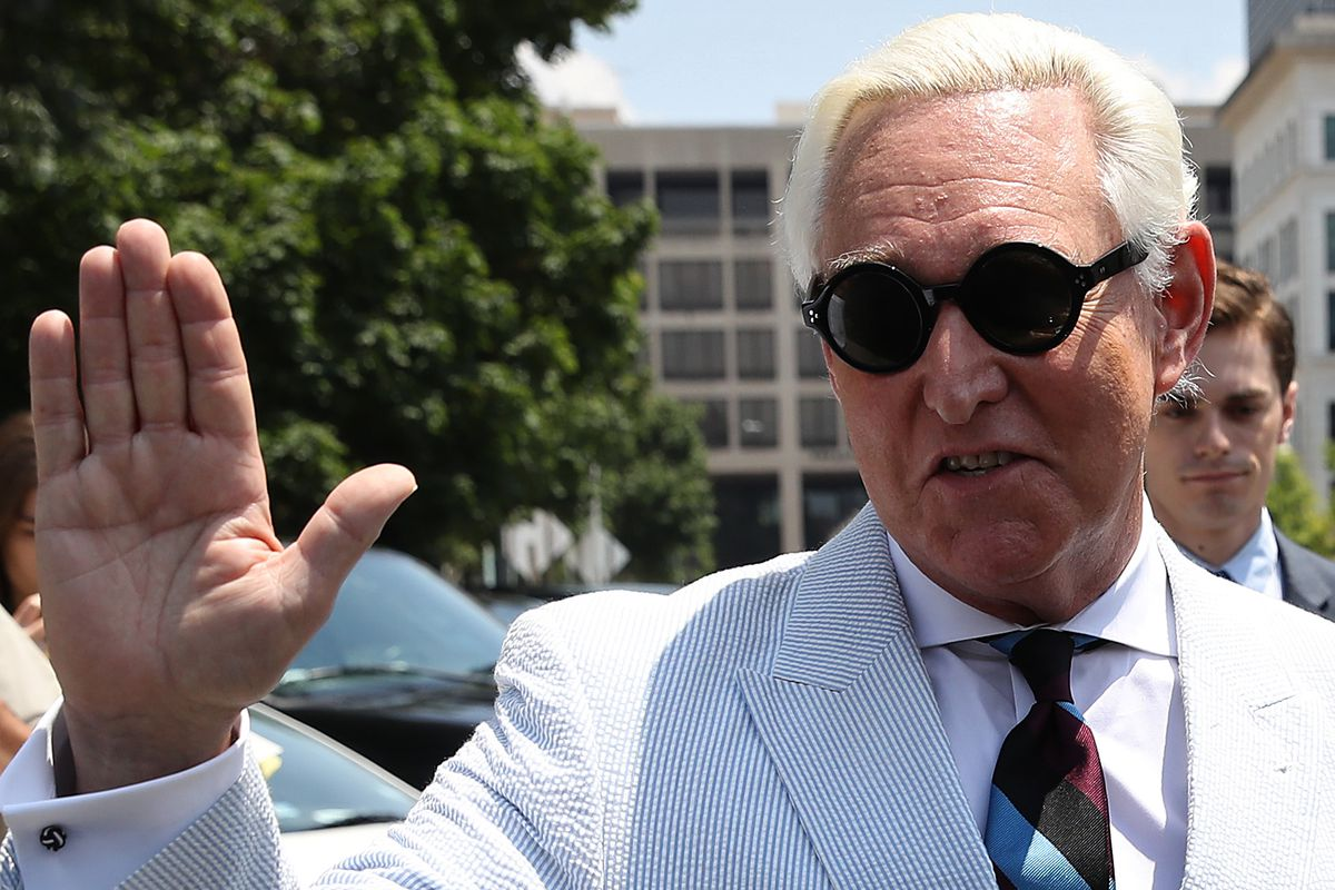 Roger Stone, former adviser to US President Donald Trump, holds up a hand to reporters.