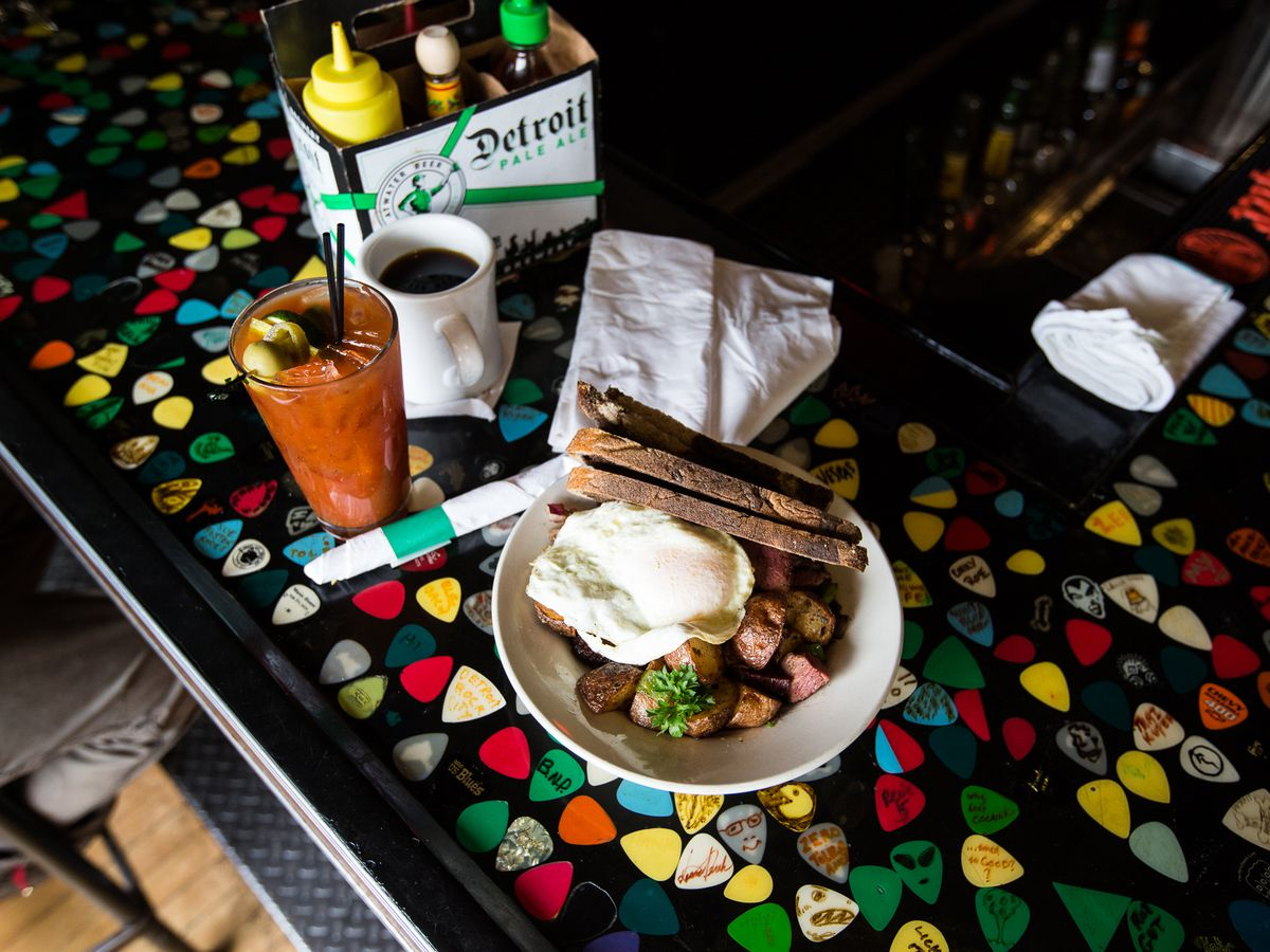 An over easy eggs sits on top of red potatoes with slices of toast on a bar embedded with guitar picks.