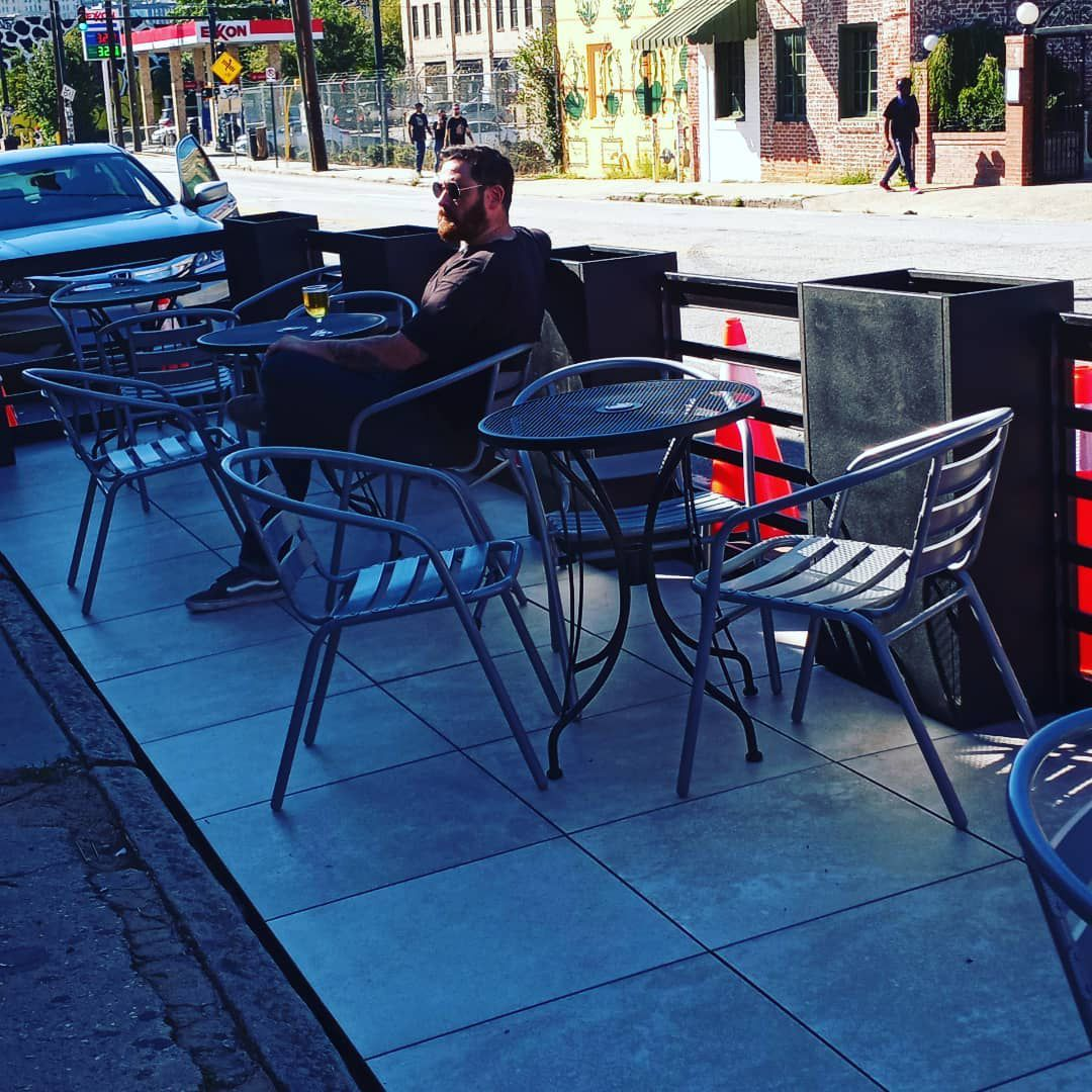 A bearded man clad in black with sunglasses on lounges at one of the black metal tables on the parklet dining area at Joystick Gamebar on Edgewood Avenue in Atlanta.