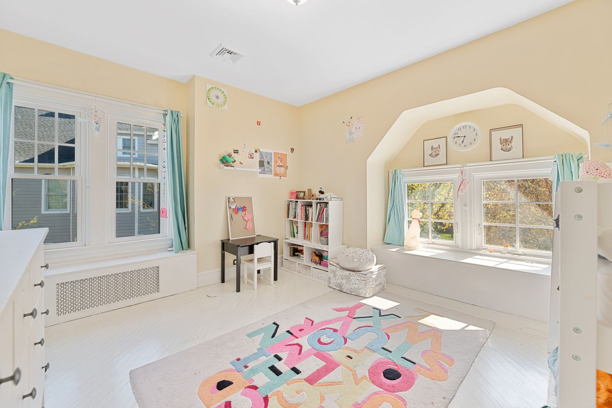 A children's bedroom with light yellow walls, encased windows, and white furniture.