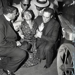 Grief-stricken mother of Emmett L. Till kneels in prayer beside casket of her son as it arrives from Mississippi at Central Station. Clergymen with Mrs. Mamie E. Bradley are Bishop Louis H. Ford (right) of St. Paul's Church of God in Christ and Bishop Isaiah Roberts, Roberts Teple, Church of God in Christ.