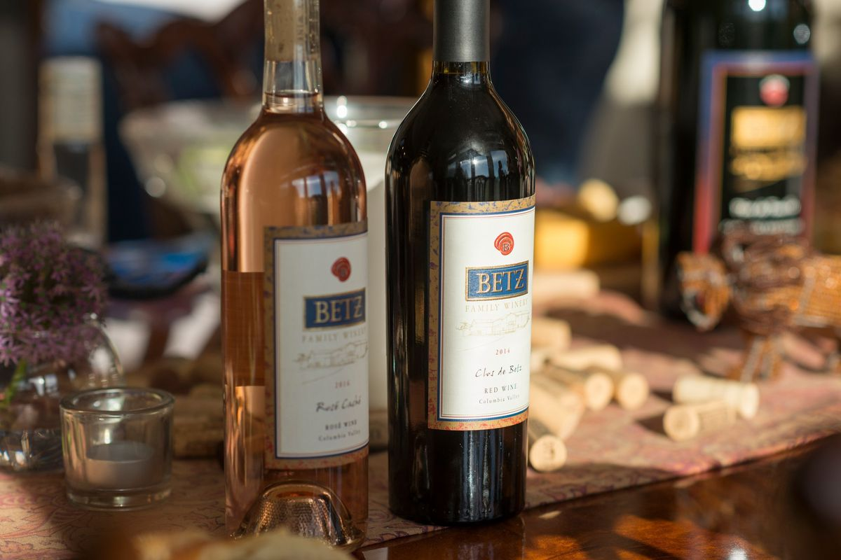 A bottle of red wine to the right; a bottle of white to the left with the Betz Family WInery label on both, and a cheeseboard in the backrgound