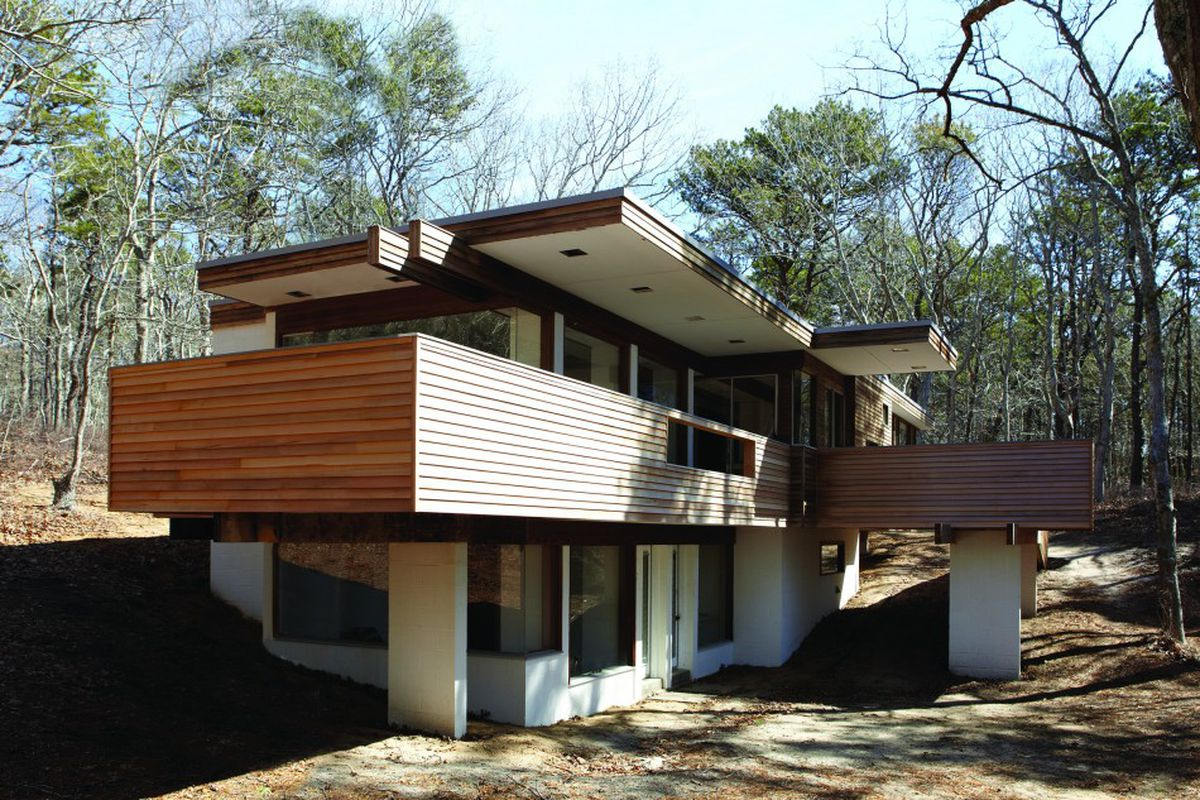 Exterior shot of flat-roofed home with massive cantilevering decks and eaves over a solid stone base.