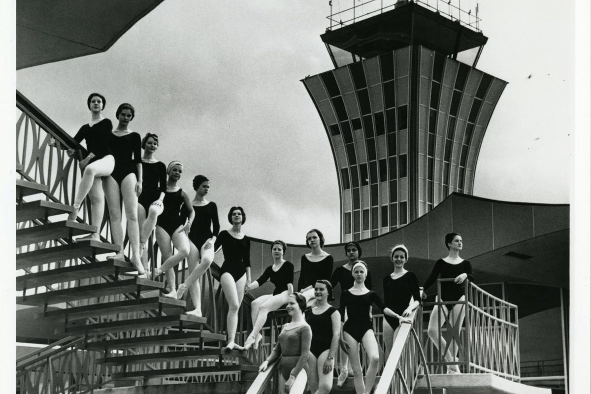 Black and white photo of ballet dancers in leotards, tights, etc., in front of a midcentury modern airport control tower
