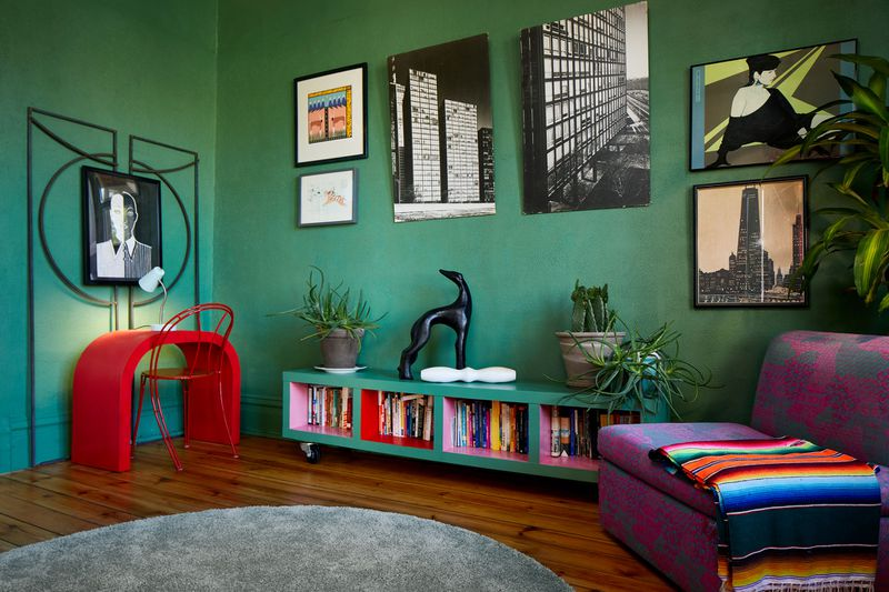 Artworks of various sizes hang on a dark green wall. A purple armchair is nearby.