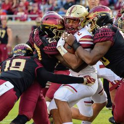 A host of Seminoles rush to the ball for a crushing tackle of Boston College's star running back AJ Dillon.