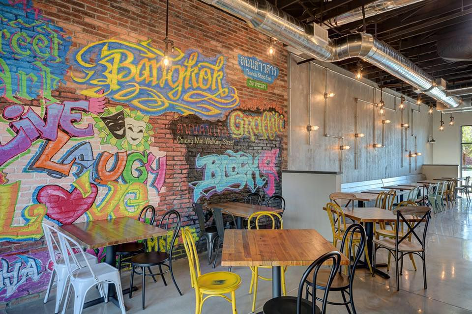 A restaurant interior featuring a brick wall covered in colorful graffiti that references Bangkok