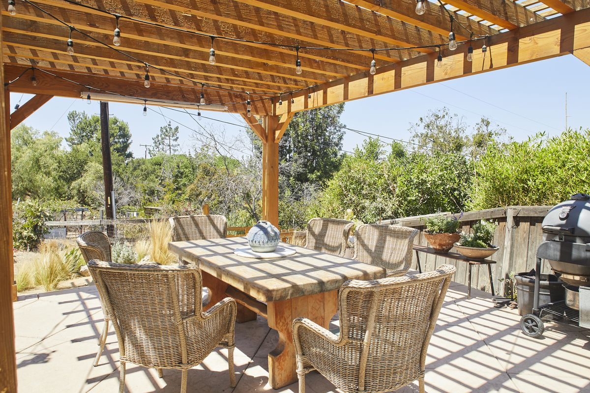 A patio has a large trellis that covers a large table and wicker chairs.
