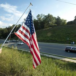 FILE - In this Monday, Aug. 27, 2012 file photo, Sue Funderburk holds a U.S. flag as she pays her respects for Marine Staff Sgt. Greg Copes of Lynch Station,Va. as the procession for his funeral heads to his burial site in Altavista, Va. So far, 1,980 American soldiers have been killed in Afghanistan. A recent surge of insider attacks by Afghan security forces has claimed the lives of 40 allied soldiers, according to a report by the Brookings Institution. Americans may have pushed the war from their everyday consciousness. But losing neighbors and classmates keeps turning a distant war into an anguished and very personal reality.