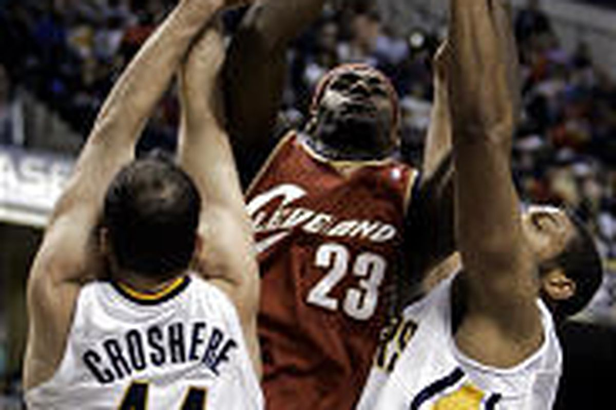 Cleveland's LeBron James (23) tries shooting between Indiana's Austin Croshere, left, and David Harrison during the second quarter Thursday.