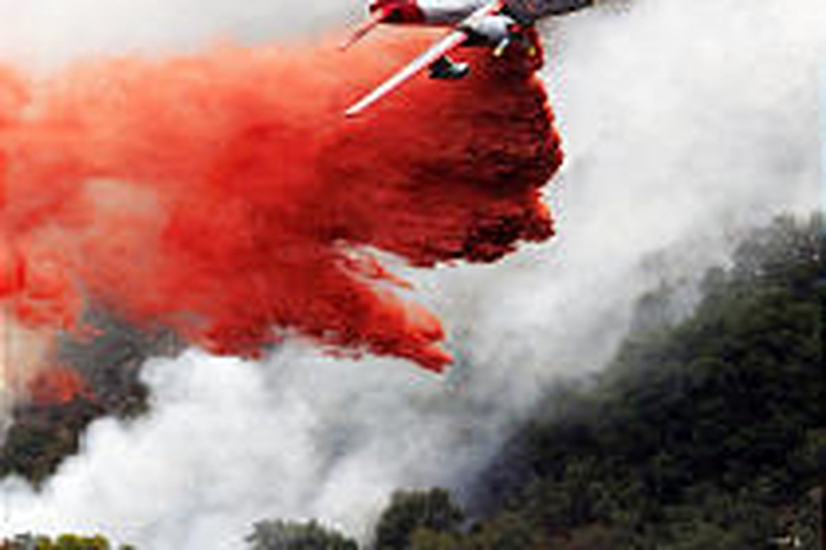 A U.S. Forest Service air tanker drops fire retardant Thursday in Oak Park, Calif. At least one home was lost.