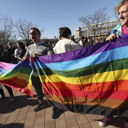 Rally organizer and BYU student Ryan Jenks, center, holds flags with fellow students Kate Lunnen and Alex Nielsen as LBGT supporters rally on Brigham Young University's campus in Provo on Wednesday, March 4, 2020.