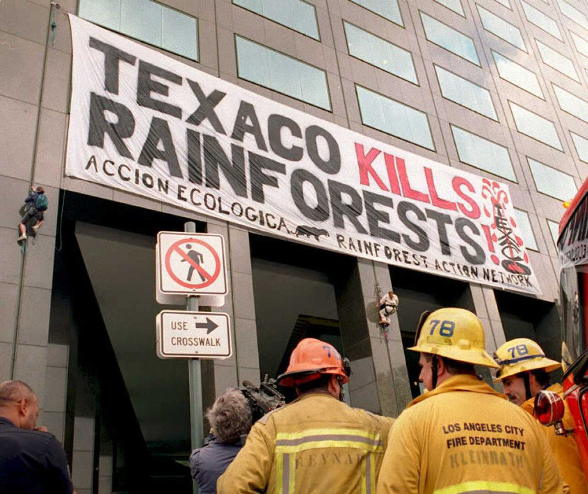 """A sign affixed to a corporate building by environmental activists reads, """"Texaco kills rainforests."""""""