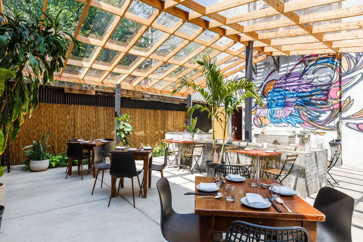 Plants and a mural decorate the outdoor dining area