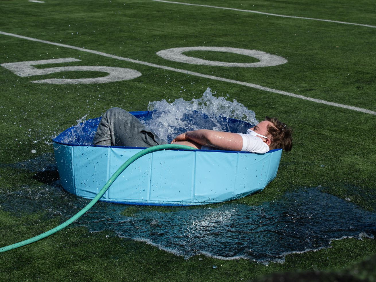 A student jumps into a wading pool filled with snow and water for St. Patrick High School's version of the Polar Plunge.