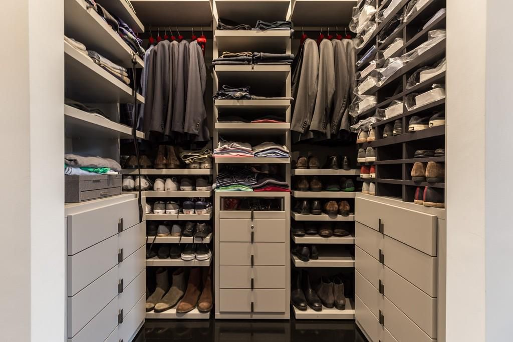 A walk-in closet with shoes and clothes put away.