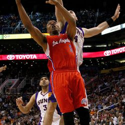Los Angeles Clippers' Caron Butler shoots past Phoenix Suns' Marcin Gortat (4), of Poland, during the first half of an NBA basketball game, Thursday, April 19, 2012, in Phoenix.