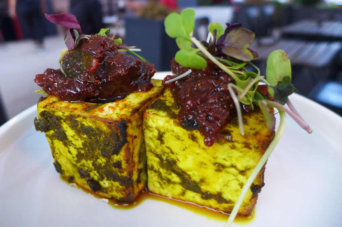 Two white cubes veined with green cutney and topped with brown relish.