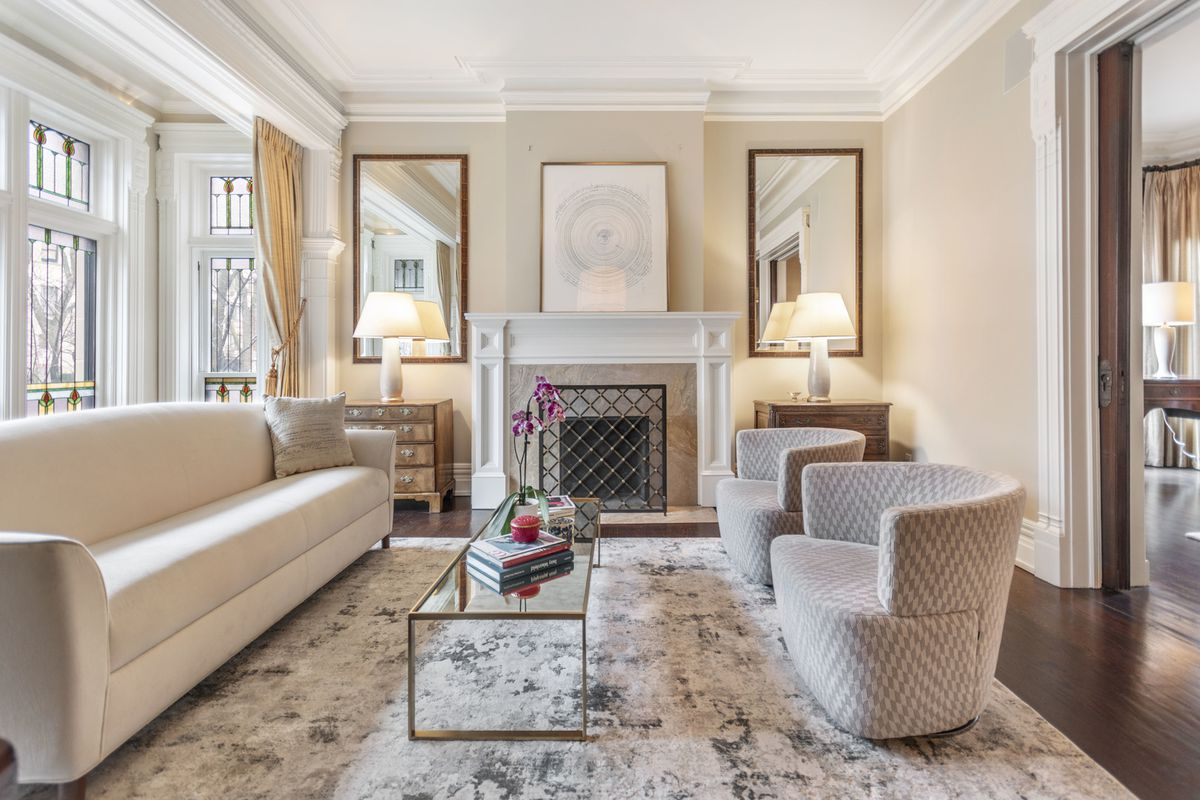 A fireplace stands in the middle of a formal living room with beige walls and white trimwork.