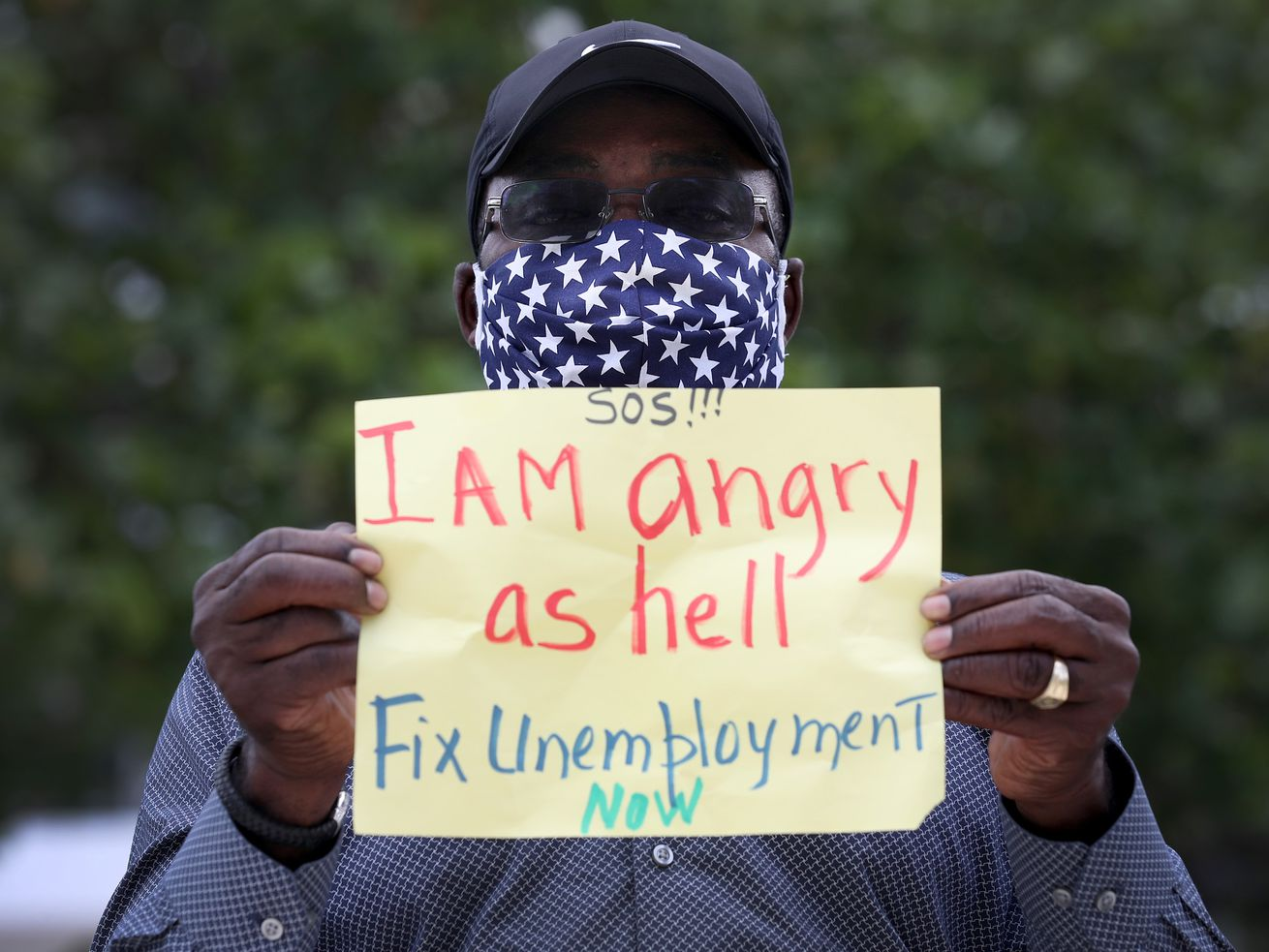 """The man, in a blue mask with white stars, holds a sign written on a yellow piece of paper. It reads: """"SOS!!! I AM angry as hell Fix Unemployment NOW."""""""