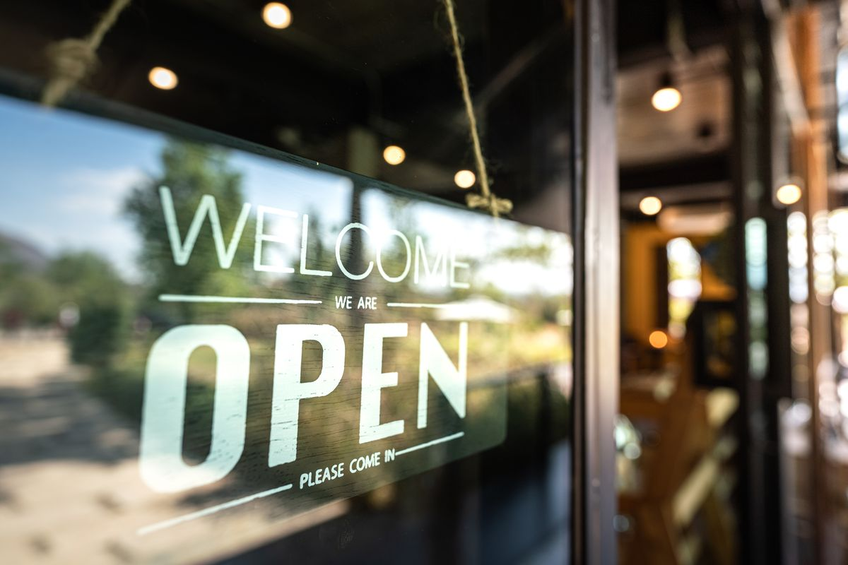 """A sign in a restaurant window says """"Welcome, We Are Open, Please Come In"""""""
