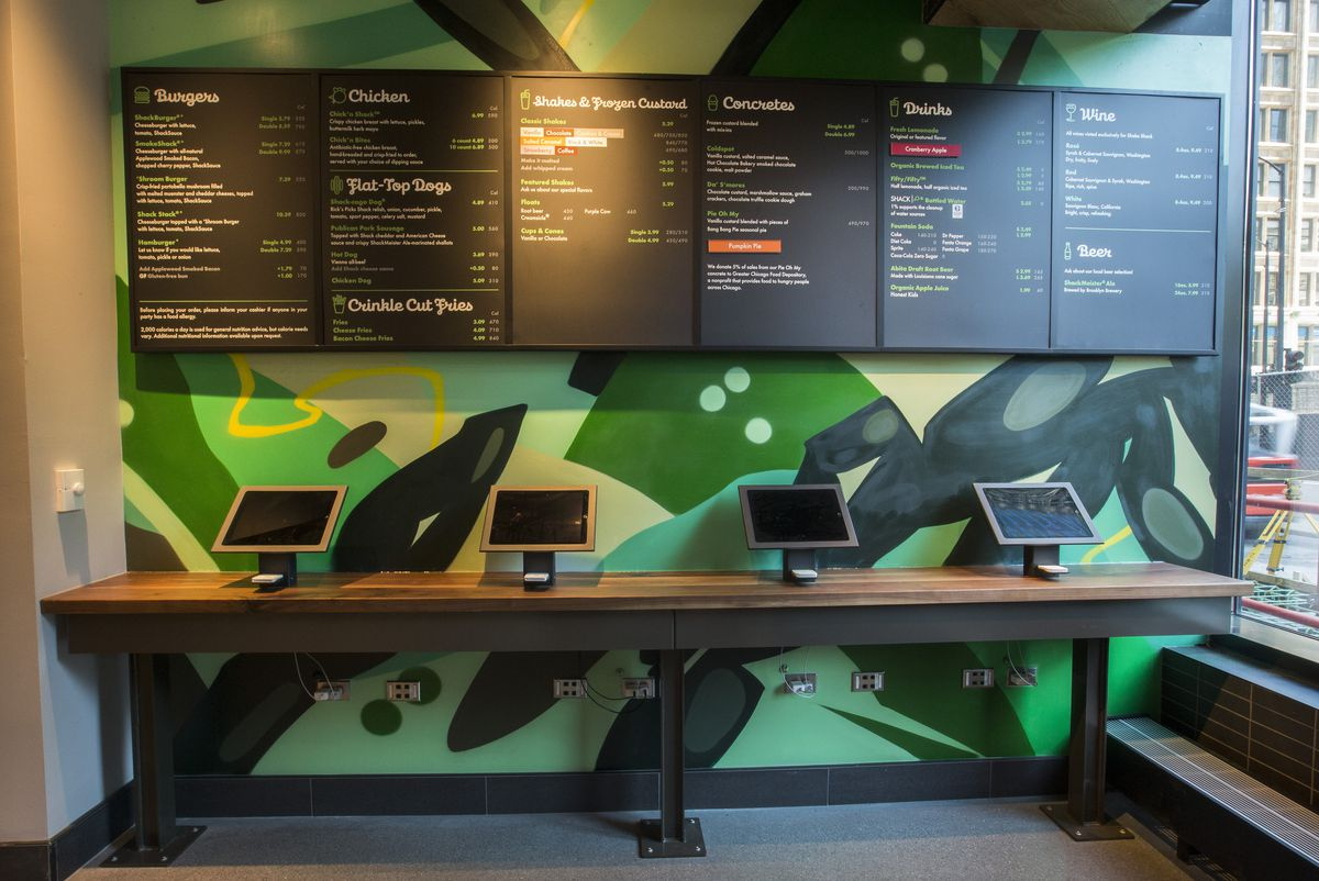 A fast-food restaurants menu on six menu boards with four computer screens mounted on a table.