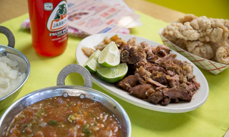 A platter of meat, a bowl of salsa, a paper container of chicharron, and a red Jarritos soda sit on a green tablecloth.