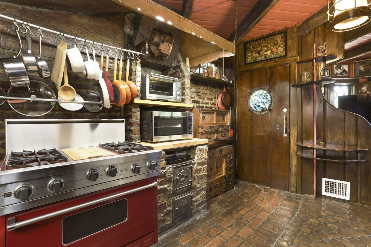 The kitchen with a stainless steel range and brick walls.